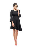 Belleza latina femenina blanda en el vestido negro que camina y que mira abajo Foto de archivo
