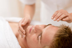 Belleza masculina - hombre que recibe masaje facial Imagen de archivo libre de regalías