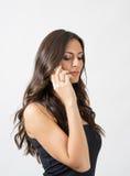 Belleza morena bronceada del pelo largo que habla en el teléfono móvil que mira abajo Foto de archivo