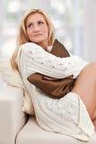 Belleza, mujer del blondie en un sofá con una almohadilla Imagenes de archivo