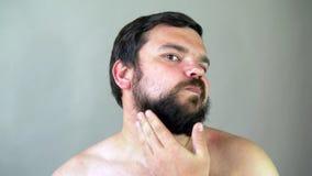 Belleza, preparación y concepto de la gente - hombre joven que mira para duplicar y que afeita la barba con el condensador de aju almacen de video