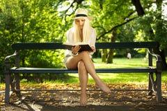 Belleza que se sienta en una lectura del banco en el sol Imagenes de archivo
