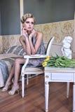 Belleza rubia en un viejo cuarto con los tulipanes Foto de archivo libre de regalías