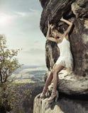 Belleza rubia que presenta en una roca peligrosa Imagen de archivo libre de regalías