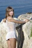 Belleza sonriente en roca cerca del mar Foto de archivo