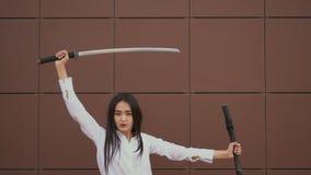 Belleza tailandesa dramáticamente tirar de la espada de la envoltura, y dar vuelta rápidamente a la cabeza a la cámara almacen de metraje de vídeo