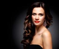 Belleza Woman modelo con el pelo ondulado largo de Brown Pelo sano y maquillaje profesional hermoso Labios rojos y ojos ahumados fotos de archivo libres de regalías