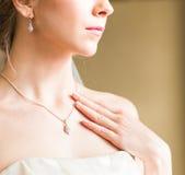 Belleza y concepto de la joyería - mujer que lleva el colgante brillante del diamante fotografía de archivo