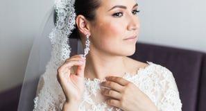 Belleza y concepto de la joyería - mujer que lleva los pendientes brillantes del diamante imagen de archivo
