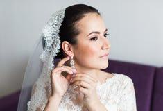 Belleza y concepto de la joyería - mujer que lleva los pendientes brillantes del diamante fotografía de archivo libre de regalías