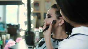Belleza y concepto del maquillaje - retrato del primer de la mujer hermosa que consigue maquillaje profesional metrajes