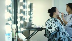 Belleza y concepto del maquillaje - retrato del primer de la mujer hermosa que consigue maquillaje profesional almacen de metraje de vídeo