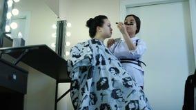 Belleza y concepto del maquillaje - retrato del primer de la mujer hermosa que consigue maquillaje profesional almacen de video