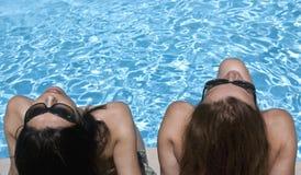 Bellezas en el poolside Fotos de archivo libres de regalías