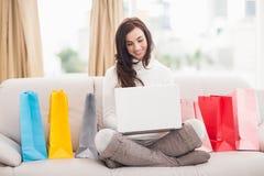 Bellezza castana facendo uso del suo computer portatile sullo strato Immagine Stock Libera da Diritti