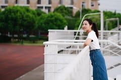Bellezza cinese asiatica dello studente di college nel campo da giuoco della scuola della città universitaria Fotografia Stock