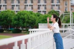 Bellezza cinese asiatica dello studente di college nel campo da giuoco della scuola della città universitaria Fotografia Stock Libera da Diritti