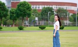 Bellezza cinese asiatica dello studente di college nel campo da giuoco della scuola della città universitaria Immagini Stock Libere da Diritti
