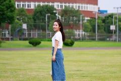 Bellezza cinese asiatica dello studente di college nel campo da giuoco della scuola della città universitaria Immagine Stock