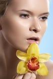 Bellezza con il fiore dell'orchidea, benessere, cura di pelle, bello fronte della stazione termale Fotografia Stock