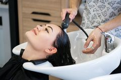 Bellezza e concetto della gente - giovane donna felice con la testa di lavaggio del parrucchiere al salone di capelli fotografia stock libera da diritti