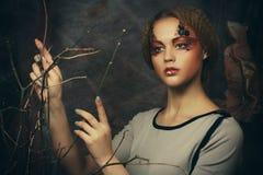 Bellezza e concetto di arte: La giovane donna con luminoso compone con i rami asciutti Fotografie Stock