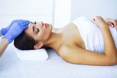 Bellezza e cura Bella ragazza che si trova sulle Tabelle di massaggio nel salone della stazione termale Massaggio facciale Mani d immagine stock libera da diritti