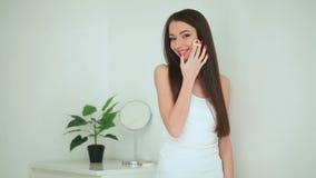 Bellezza e cura Donna che applica crema su pelle La bella giovane donna con pelle fresca pulita tocca il suo fronte facciale video d archivio