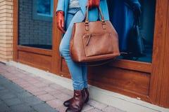 Bellezza e modo Cappotto d'uso alla moda e guanti della donna alla moda, tenenti la borsa marrone della borsa immagine stock libera da diritti