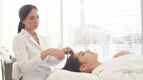 Bellezza ed immagine di cosmetologia del fronte della giovane donna che ha massaggio di fronte nel salone della stazione termale stock footage