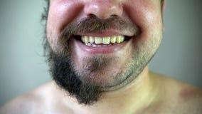 Bellezza, governare e concetto della gente - giovane che guarda allo specchio e che rade barba con il regolatore o il rasoio elet stock footage