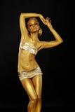 Bellezza luminosa. Bella donna esile con la posa dorata della pelle. Bodyart immagine stock libera da diritti