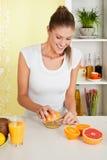 Bellezza, ragazza che produce il succo di arancia Fotografie Stock Libere da Diritti