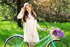 Bellezza stupefacente Colpo orizzontale di bella giovane donna in vestito che regola cappello mentre tenendo retro bici con il ca Immagine Stock