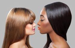 Bellezze nere e caucasiche con capelli diritti Immagine Stock