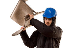 Belligerent thug threatening with a raised chair. Belligerent young male thug in a hoodie and hardhat making a threatening gesture with a wooden kitchen chair Royalty Free Stock Photo