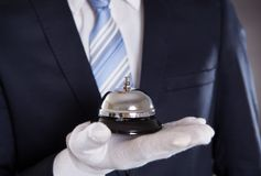 Bellman Holding Bell. Midsection of bellman holding bell against black background Royalty Free Stock Photography