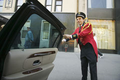 Bellman in red jacket opens limo door in front of Helmsley Park Lane Hotel on Central Park West, in Manhattan, New York City, NY Stock Images