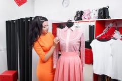 Bello acquisto della giovane donna in un negozio di vestiti Fotografia Stock