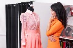 Bello acquisto della giovane donna in un negozio di vestiti Immagini Stock