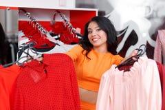 Bello acquisto della giovane donna in un negozio di vestiti Immagine Stock