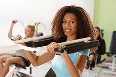 Bello addestramento afro della donna sulla macchina del peso Fotografie Stock