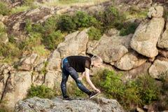 Bello addestramento biondo allegro della ragazza, allungante sulla roccia in canyon Immagine Stock Libera da Diritti