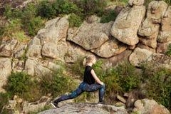 Bello addestramento biondo allegro della ragazza, allungante sulla roccia in canyon Immagine Stock
