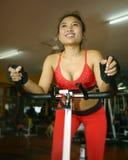 Bello addestramento felice asiatico sudato della donna che sorride duro ciclando e guidando sull'allenamento statico della bici a Immagini Stock Libere da Diritti