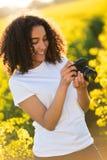 Bello adolescente afroamericano della ragazza della corsa mista che usando macchina fotografica Fotografia Stock