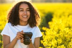 Bello adolescente afroamericano della ragazza della corsa mista che usando macchina fotografica Fotografie Stock