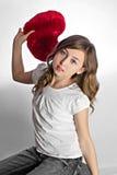 Ragazza teenager con il cuscino a forma di del cuore Fotografia Stock