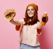 Bello adolescente con l'hamburger rosso e la bevanda della tenuta del cappello e dei capelli in entrambe le mani fotografia stock libera da diritti