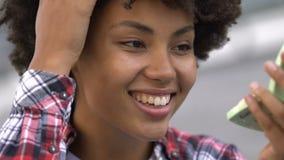 Bello adolescente riccio-dai capelli che corregge trucco, sembrante specchio disponibile archivi video